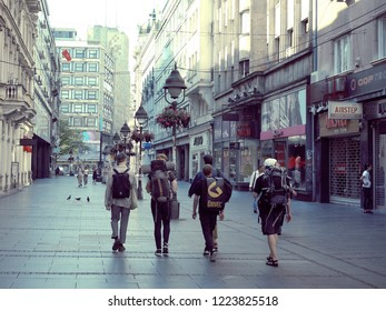 BELGRADE, SERBIA - JULY 20, 2018: rear view young travelers with backpacks walking in central pedestrian street