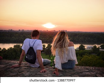 BELGRADE, SERBIA - JULY 20, 2018: young couple sitting on a wall of Kalemegdan fortress and looking at the sunset on the Danube river