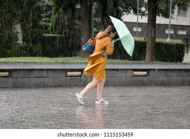 Belgrade, Serbia - June 14, 2018: One young woman running under umbrella in the sudden  heavy spring windy rain in the city park , holding a bottle of water