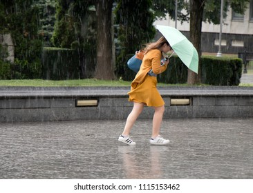 Belgrade, Serbia - June 14, 2018: One young woman running under umbrella in the sudden  heavy and windy  spring rain in the city park , holding a bottle of water