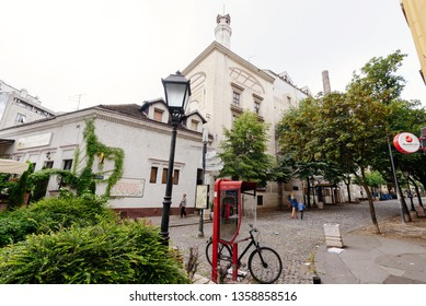 Belgrade, Serbia - June 16, 2018. Historic place Skadarlija with phone booth, trees, lamppost, bicycle and cobbled lane in downtown. Bohemian street with bars, restaurants and murals.