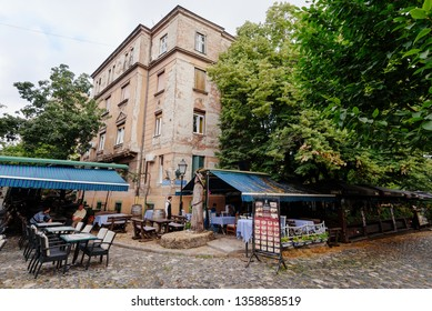 Belgrade, Serbia - June 16, 2018. Historic place Skadarlija with summer cafe terraces, trees, cobbled lanes and alleys in downtown. Bohemian street with bars and restaurants - popular landmark.