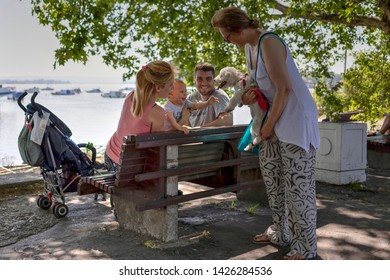 Belgrade, Serbia, June 16th 2019: Woman with doggy meets couple with baby at the Danube riverside promenade in Zemun