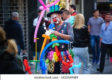 Belgrade, Serbia - June 2,2019: Balloon challenge  in the center of Belgrade, Fully costumed clown making balloon animals and shapes  on a crowded Belgrade street, Concept of entertainment