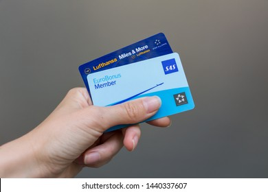 Belgrade, Serbia - June 29, 2019: Young woman holds SAS Eurobonus Member card and Lufthansa Miles & More card which allow travelers to collect and spend miles on Star Alliance airlines flights.