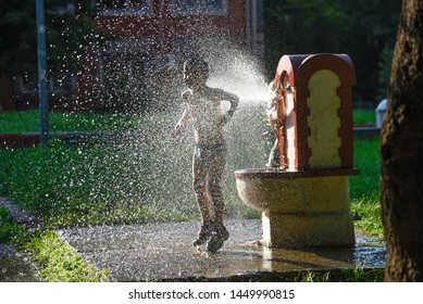 BELGRADE, SERBIA - JUNE 7, 2019: Unrecognisable kids playing with water fountain on a hot summer day in the park in Belgrade, Serbia.
