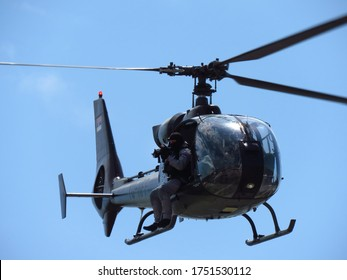 Belgrade, Serbia - June 7, 2020. Police Day. A member of the special police forces, flying in a helicopter and holds a machine gun in his hands.
