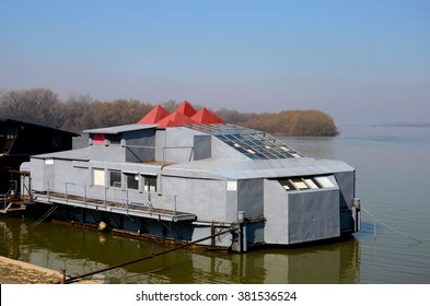 Belgrade, Serbia - March 20, 2015: A grey metal floating platform on the bank of Sava River often used as gym play area for children moored and anchored to the shore with red pyramid shaped roofs.