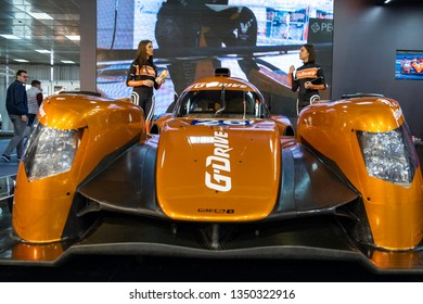 Belgrade / Serbia - March 23rd 2019: Beautiful hostess girls standing next to the racing sports car, promoting G-DRIVE octane fuel, at the Belgrade Car and Motor Show (54th International Motor Show)