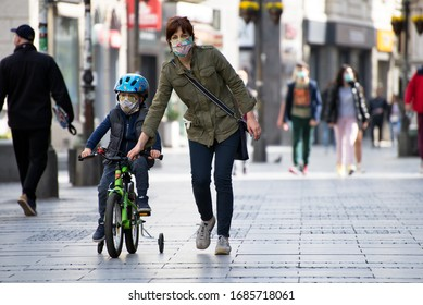 Belgrade, Serbia - March 28, 2020: Mother and a small child on the city streets wearing face masks to protect from corona virus. COVID - 19 pandemic. Street view in city center