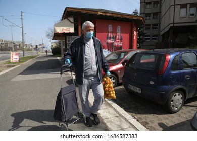 BELGRADE, SERBIA - MARCH 28, 2020: Man in a mask carries a bow. As the Corona Virus continues to spread all over Serbia, government imposed curfew to prevent the spread of coronavirus disease.