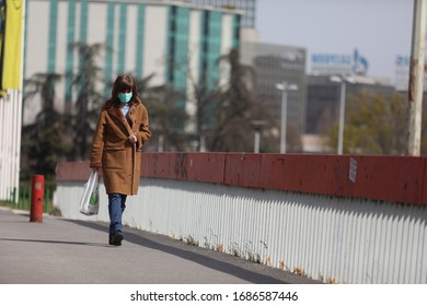 BELGRADE, SERBIA - MARCH 28, 2020: Woman with mask walking in street. As the Corona Virus continues to spread all over Serbia, government imposed curfew to prevent the spread of coronavirus disease.