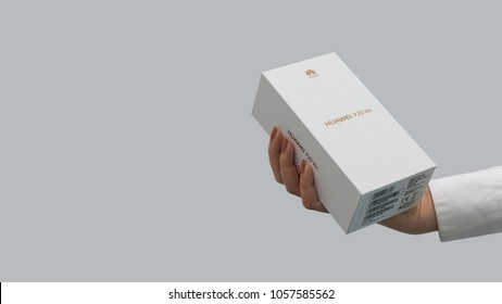 Belgrade, Serbia - March 29, 2018: New Smartphone, Huawei P20 lite, in original box, is holded with a hand on isolated background