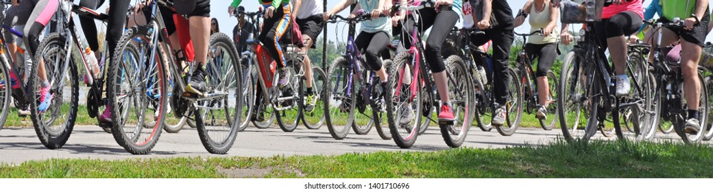 Belgrade, Serbia; May 19, 2019. Bicycle day. Bicycles and cyclists. Just bicycle wheels and legs with sports footwear.