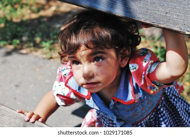 Belgrade, Serbia - May 23, 2009: A gypsy girl is playing hiding on a wooden bench