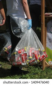 """Belgrade, Serbia - May 25, 2019: Detail of Festival """"Belgrade Manifest"""" held on Kalemegdan fortress. Young man carries a plastic bag with empty recyclable cans of Coca Cola."""