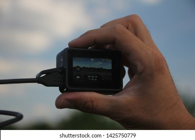 Belgrade, Serbia - May, 25 2019: GoPro Hero 7 Black action camera with USB cable in the male hand.