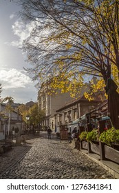 BELGRADE, SERBIA - NOVEMBER 17, 2014: Skadarlija street (also known as Skadarska) at fall with its typical cobblestone pavement cafes and restaurants and tourists passing by