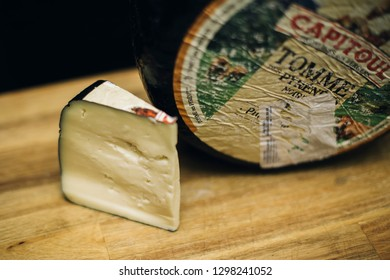 BELGRADE, SERBIA - NOVEMBER 22, 2018: Detail of Tomme Des Pyrenees cheese in Belgrade, Serbia. Tomme Des Pyrenees is a French rustic cheese, usually covered in a thin black skin.
