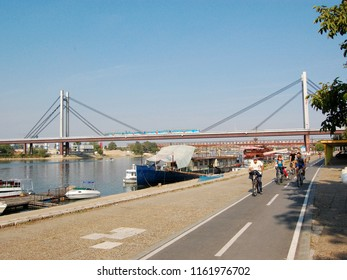 Belgrade, Serbia October 05, 2011. The new railway bridge on the Sava River. A few people ride bicycles on a bicycle trail on the right bank of the river.