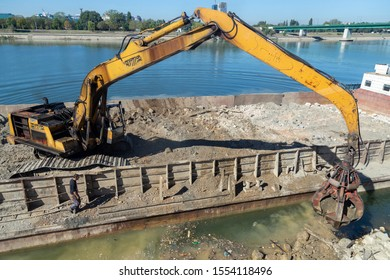 BELGRADE, SERBIA - OCTOBER 09, 2019: Hydraulic multi valve crab bucket from river barge, working on river revetment at construction site.