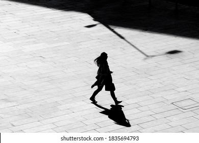 Belgrade, Serbia - October 09, 2020: Shadow silhouette of a young woman walking city square pavement,  in high angle view black and white