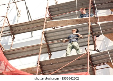 Belgrade, Serbia - October 25, 2019: Two unprotected construction workers on the scaffold during building facade reconstruction, an unsafe, hazard  and dangerous behavior