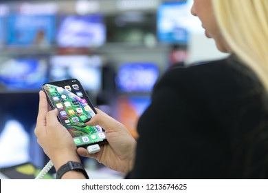 Belgrade, Serbia - October 26, 2018: New Apple iPhone XS Max mobile smartphone is displayed with apps on the screen in electronic store. Girl testing new gadget in hands.