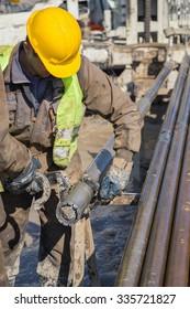 BELGRADE, SERBIA - OCTOBER 28, 2015: Worker checks a diamond core drill bit.  Made with shallow dof.