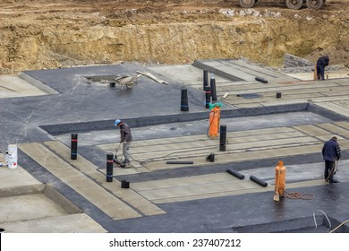 BELGRADE, SERBIA - OCTOBER 30: Foundation insulation workers at ground waterproofing works. Workers melting bitumen felt and water proofing of concrete structure. At construction site in October 2014.