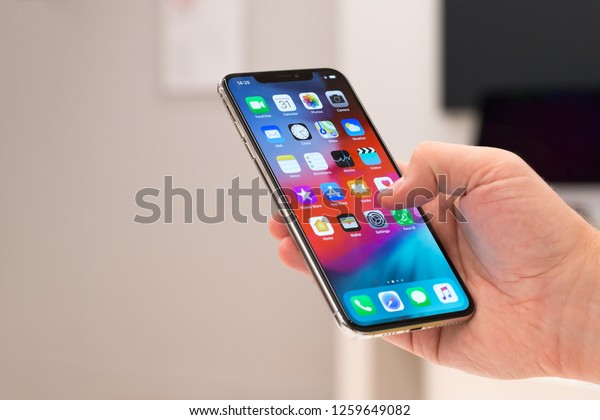 Belgrade, Serbia - October 31, 2018: New Apple iPhone XS mobile smartphone is displayed with apps on the screen in hand. Finger typing on digital gadget in electronic store.