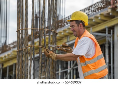 BELGRADE, SERBIA - SEPTEMBER 08, 2016: Tying reinforcing steel bars with plier and wire on construction pillars. Reinforcement work.