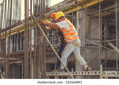 BELGRADE, SERBIA - SEPTEMBER 08, 2016: Construction workers prepare iron bars for concrete pillar at construction site. Abstract: heavy job, hard work, outdoor. Vintage style.