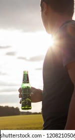 BELGRADE, SERBIA - SEPTEMBER 09, 2018 Carlsberg globaly distributed pale lager beer produced by Carlsberg Group ,Man tourist standing in a field in europe holding a drink enjoying in magnificent day