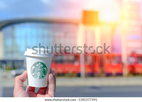 BELGRADE, SERBIA - SEPTEMBER 10 2018 Hand holding Starbucks paper cup with take out coffee at city street