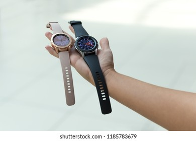 Belgrade, Serbia - September 13, 2018: New Samsung Galaxy Watch 46 mm - SM-R800 and 42 mm - SM-R810 are displayed in hand against isolated background. Two gadgets, showing time on the screen.