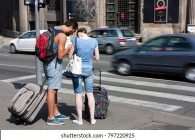 Belgrade, Serbia - September 17, 2017 : Young people traveling couple with rolling suitcases and backpacks trying to orientate and find their way and direction in the city streets. from behind