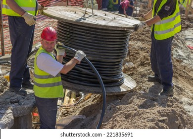 BELGRADE, SERBIA - SEPTEMBER 30:  Installing new ground infrastructure in the street. Workers unrolls electrical cable. Selective focus. At street Vojvode Stepe in September 2014.