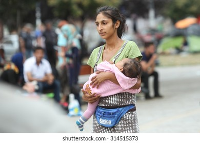 BELGRADE, SERBIA - SEPTEMBER 5 : A young Syrian woman holding a child in a park near the train station, waiting for the transport to the European Union on September 5th, 2015 in Belgrade, Serbia.