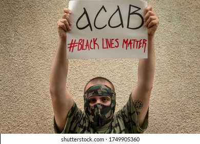 "BELGRADE SERBIA-May 05 2020 Man with mask protests for black rights.Banner saying ""ACAB Black lives matter"" fights for justice and against police brutality.Demonstrations caused by George Floyd's case"