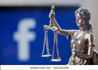 Belgrade/SERBIA - June 18th 2019: Blind folded Lady Justice statue in front of a laptop with social network Facebook logo on the screen, depicting the launch of Facebook's crypto currency Libra credit