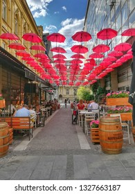 Belgrade/Serbia - May 18, 2018: A restaurant in Kralja Petra Street, in the centre of Belgrade, on sunny spring day.Red umbrellas hang above the street, parasols used as street decoration.