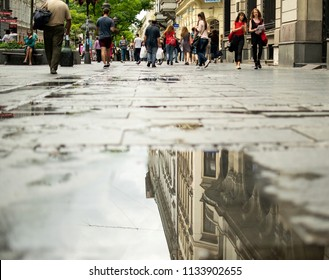 Belgrade,Serbia-July 12,2018.Image shows people walking at the Knez Mihailo street and the reflection of a building on the  rain water.