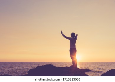 Belief concept Woman raising hands to pray for blessings During the sunset image Vintage style