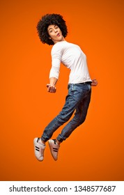 I believe I can fly! Ecstatic young man jumping in air and smiling, orange studio background