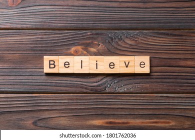 believe word written on wood block. believe text on table, concept.
