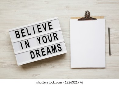 'Believe in your dreams' word on modern board, noticeboard, pencil over white wooden surface, overhead view. Top view, flat lay, from above.