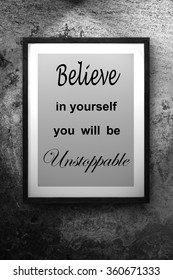 believe in your self you will be unstoppable quote on the photo frame cement background