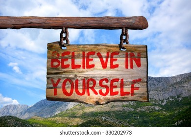 Believe in yourself motivational phrase sign on old wood with blurred background