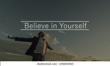 Believe in yourself sign above a young businessman in a suit enjoying his freedom and professional independence with arms wide open standing under evening sky.